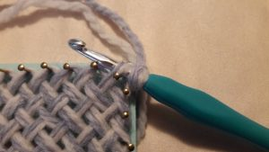 Crochet hook through the corner loop